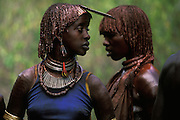 Two Hamar women dance at a bull jump, a ritual at which a young man runs across the backs of a number of bullocks in order to become eligible for marriage, in South Omo, Ethiopia. Their hair and neck are coated in butter and red ochre and they have scarifications on their arms and shoulders. A blue cotton singlet and safety-pin necklace add a touch of modernity to the dress of one of the women. The 40,000-strong, cattle-herding Hamar are among the largest of the 20 or so ethnic groups which inhabit the culturally diverse Omo region in south-west Ethiopia.