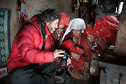 Matthieu Paley showing images on his camera to Kyrgyz women in Afghanistan...The Kyrgyz settlement of Ech Keli, above Chaqmaqtin lake, Er Ali Boi's camp...Trekking through the high altitude plateau of the Little Pamir mountains, where the Afghan Kyrgyz community live all year, on the borders of China, Tajikistan and Pakistan.