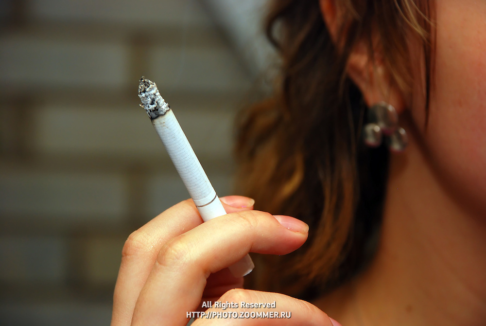 Smoking woman with cigarette between fingers
