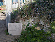 Sign stating that house at risk of coastal erosion is still occupied, Happisburgh, Norfolk, England