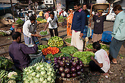 A buyer negotiates with fruit and vegetable vendors at a market in the slums near the main train station in Dahaka, Bangladesh.  Nearly 20 percent of Dhaka's more than seven million residents live in the slums.