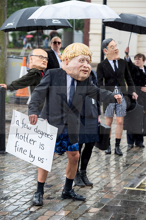 """© Licensed to London News Pictures;28/08/2020; Bristol, UK. Circus and physical theatre performers dressed as political figures Boris Johnson, Michael Gove, Jacob Rees-Mogg, Dominic Cummings, Donald Trump and Vladimir Putin, with masks made by Bim Mason, Director of Circomedia @bigheadbim and @rapiddissent on Instagram, do a walkabout as part of Extinction Rebellion protest in Bristol Harbourside on the first day of a bank holiday weekend of protest action titled """"Bristol Rebellion: We Want To Live"""". XR are protesting in Bristol and other cities in the UK against climate change, leading up to a protest in London starting on 01 September. XR say that despite clear scientific evidence of the deadly climate and ecological emergency, the UK government are refusing to take the urgent action needed to avoid mass extinction. XR say we need politicians to support the Climate and Ecological Emergency Bill. During the coronavirus covid-19 pandemic, climate change is being forgotten but it is still an emergency that is happening, the elephant in the room. Photo credit: Simon Chapman/LNP."""