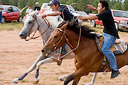 """09 SEPTEMBER 2007 -- ST. MICHAELS, AZ: Jockeys DOMINICK WHITEHORSE, left, and JOHNNY GOLDTOOTH cross the finish line of the five mile race at a traditional Navajo Horse Race in the summit area of the Navajo Indian reservation about 10 miles west of St. Michaels, AZ. Whitehorse won the race. Traditional horse racing is making a comeback on the Navajo reservation. The races are run on improvised courses that vary depending on the local terrain. Use of saddles is optional (except in the """"Cowhand Race"""" which requires a western style saddle) and many jockeys ride bareback. The distances vary from one mile to as long as thirty miles. Traditional horse races were common until the 1950's when they fell out of favor, but there has been a resurgence in traditional racing since the late 1990's and now there is a traditional horse racing circuit on the reservation. The race was organized by the Begay family of Steamboat, AZ and run on private land about three miles from a paved road.  Photo by Jack Kurtz"""