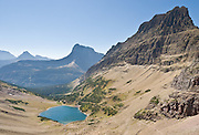 """Glacier National Park, Montana, USA: Hike to Ptarmigan Lake beneath the Ptarmigan Wall, then up to Ptarmigan Tunnel 11.2 miles round trip with 2500 feet gain. (A side trail departs at Ptarmigan Falls to visit Iceberg Lake, which can be a separate day hike, or long extension.) Since 1932, Canada and USA have shared Waterton-Glacier International Peace Park, which UNESCO declared a World Heritage Site (1995) containing two Biosphere Reserves (1976). Rocks in the park are primarily sedimentary layers deposited in shallow seas over 1.6 billion to 800 million years ago. During the tectonic formation of the Rocky Mountains 170 million years ago, the Lewis Overthrust displaced these old rocks over newer Cretaceous age rocks. Glaciers carved spectacular U-shaped valleys and pyramidal peaks as recently as the Last Glacial Maximum (the last """"Ice Age"""" 25,000 to 13,000 years ago). Of the 150 glaciers existing in the mid 1800s, only 25 active glaciers remain in the park as of 2010, and all may disappear by 2020, say climate scientists."""