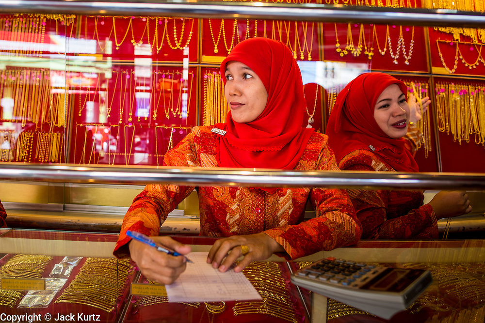 09 JULY 2013 - PATTANI, PATTANI, THAILAND: Muslim women who work in a gold shop in the market in Pattani.  Pattani, along with Narathiwat and Yala, are the only three Muslim majority provinces in Thailand.     PHOTO BY JACK KURTZ