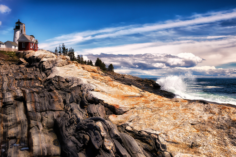 Rocks, sky and ocean dramatically fan out from Pemaquid Light
