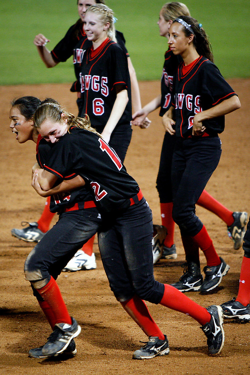 Bowie High School third baseman Alli Akina, left, is hugged by teammate Maddie Lionberger, center, after making the final out during the 5A Region 4 playoffs. The Bulldogs, down by three runs, scored five in the 6th inning and held on to defeat the San Antonio Taft Raiders and advance to the 5A State Championship Playoffs.