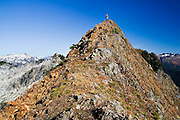 A hiker navigates a very narrow but walkable ridge under a deep blue sky on an ascent of Hurricane Peak in Glacier Peak Wilderness, Washington.