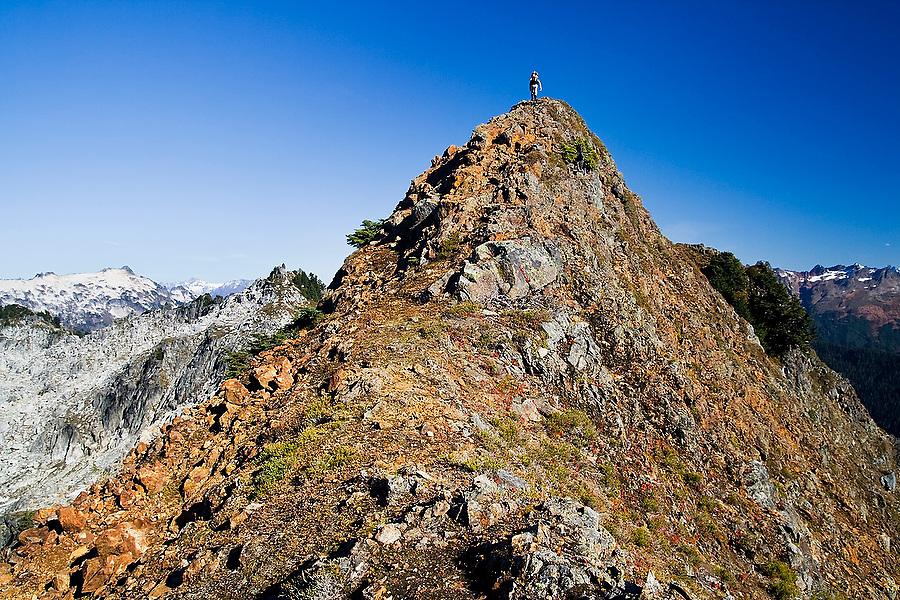 A hiker navigates a very narrow but walkable ridge under a deep blue sky on an ascent of Hurricane Peak in Glacier Peak Wilderness, Washington.