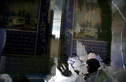 A military policeman assigned to a Police Transition Team sits in an entryway festooned with peeling posters hailing the Iraqi Police at the Joint Security Station (JSS) in central Adhamiya on Thursday April 27, 2007.
