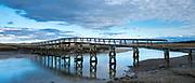Wooden boardwalk bridge over tranquil creek and salt marsh in Massachusetts, USA