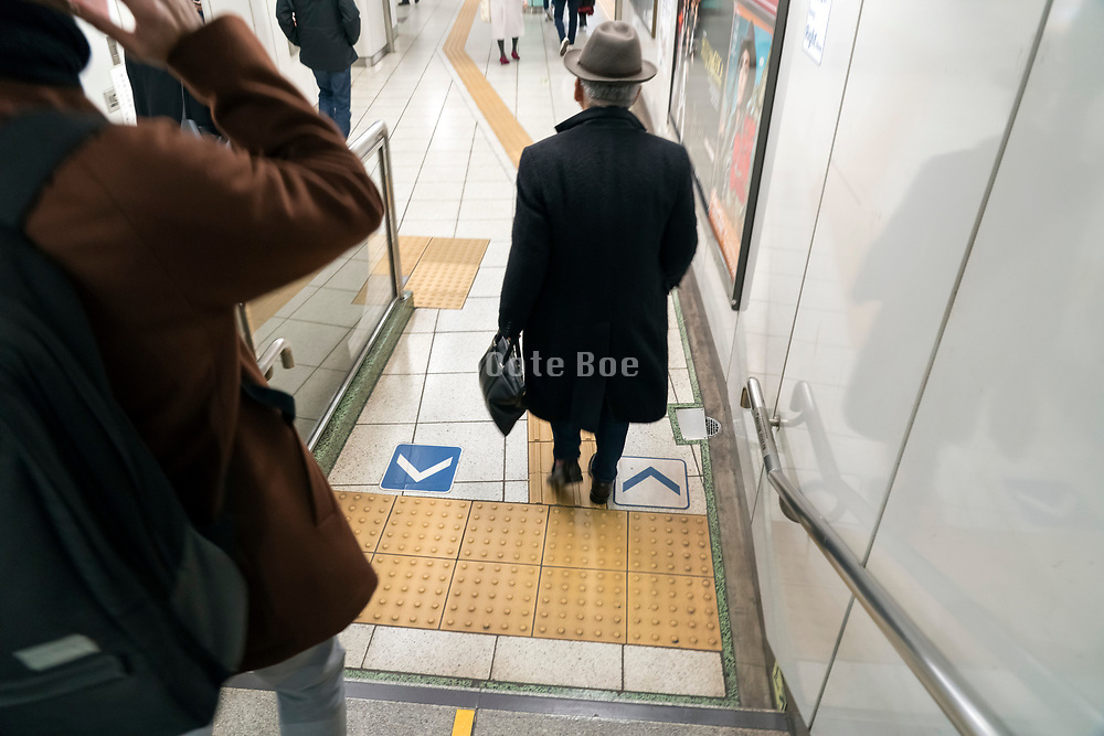 Tokyo subway with person walking on the yellow for the blind dotted tile strip called Tactile Ground Surface Indicators or TGSI