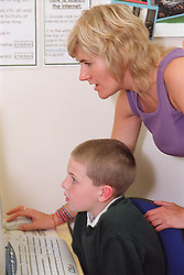 Primary school teacher helping pupil to use computer during Information and Technology lesson,