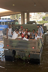 30 August, 2005. New Orleans Louisiana. Hurricane Katrina aftermath. <br /> An army truck full of evacuees from the storm backs up through the flood waters outside the Superdome to deliver its human cargo to the makeshift shelter. Approximately 20,000 storm evacuees are housed at the Superdome.<br /> Photo Credit: Charlie Varley/varleypix.com