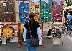 Woman looking at original art at outdoor market at Strasse des 17 Juni in Tiergarten in Berlin