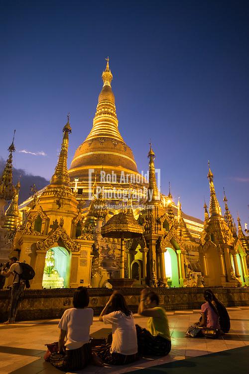 People meditating at the Shwedagon Paya in Yangon during sunset