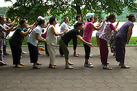 Group Massage at Hoan Kiem Lake - lakeside pavements serve as a focal point for Hanoi public life.  It is a popular spot for jogging, exercising and early morning tai chi sessions along its banks including this group giving each other a massage.