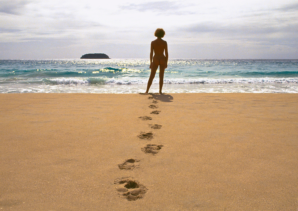 Woman's footprints in sand leading to woman standing at ocean's edge