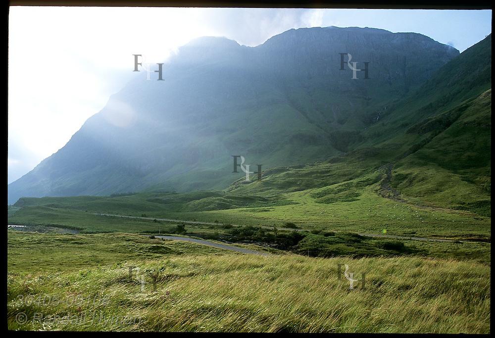 Hazy morning sun backlights mountains and fields near Clachaig Gulley, Harry Potter POA film site; Glencoe, Scotland