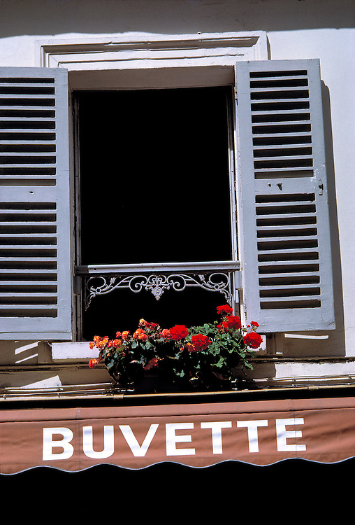 Colorful flowers fill the window box of a shuttered window in the Montmartre area of Paris, France.