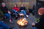 Friends catch-up with latest news and gossip while gathered around the warmt flames of a circluar fire bowl that hosts have lit in their south London back garden, on 17th April 2021, in London, England.