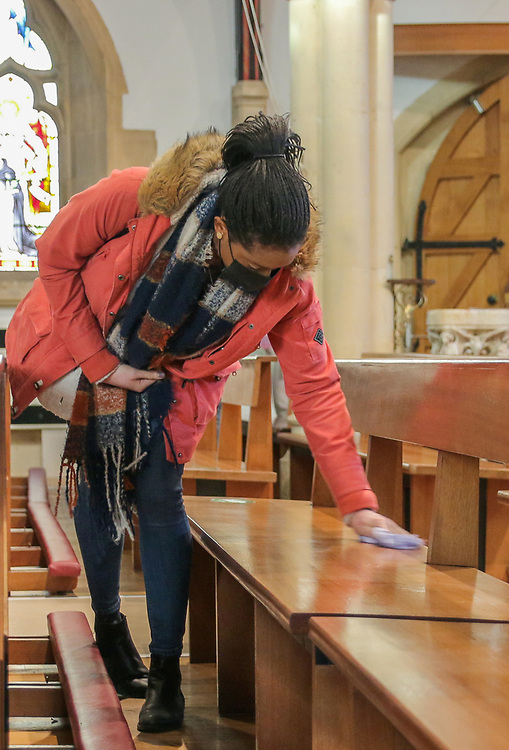 28th February, Cheltenham, England. A member of St Gregory's Catholic Church in Cheltenham wipes down the seating during the third national lockdown.