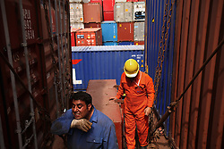A/B Seaman Fadi Joubili, of Lebanon, takes a break from tightening the lashings on the containers as they are loaded onto the vessel (to the right is Chief Officer Elsayed Ahmed Mohamed, of Egypt) in Port Said, Egypt on April 9, 2008. The Bisanzio, a feeder ship taking containers from Port Said to Beirut, is Lebanese owned, has three different nationalities aboard, and flies a St. Vincent flag. The Suez Canal is one of the most important shipping routes in the world, as it allows allows two-way water transportation - most importantly between Europe and Asia without the circumnavigation of Africa.