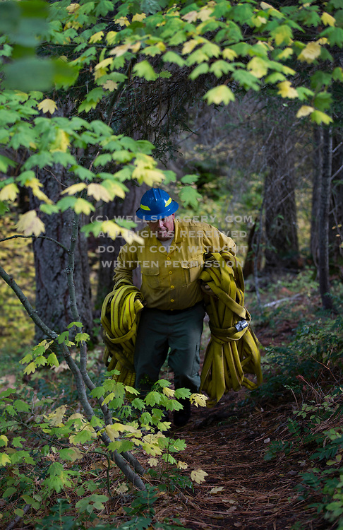 Image of a firefighter prepping his hoses in rural Washington state, Pacific Northwest by Randy Wells