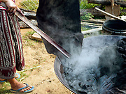 Meuay, a Iu Mien (Yao) ethnic minority woman boiling indigo dyed cotton fabric in Mak Bao (a trailing forest fruit) to fix the colour, Ban Hom Phan, Houaphan province, Lao PDR. Meuay buys the cotton fabric from a nearby Tai Deng village and after dyeing the fabric many times to build up the colour she sells it to local Iu Mien women to make their traditional clothing. One of the most ethnically diverse countries in Southeast Asia, Laos has 49 officially recognised ethnic groups although there are many more self-identified and sub groups. These groups are distinguished by their own customs, beliefs and rituals.