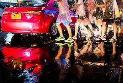 People Crossing Road at Night. Bangkok, Thailand
