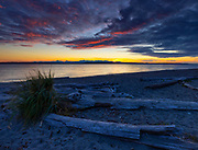 As the sun sets behind the Olympic Mountains, the red last light of day lights up the underside of clouds over Puget Sound and Marina Beach in this view from Edmonds, Washington.