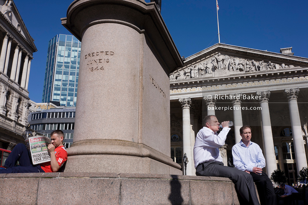 A Sun newspaper reader and businessmen below a statue at Royal Exchange behind. Behind them are the tall and solid Corinthian pillars of the 3rd Royal Exchange built in 1842 by Sir William Tite.