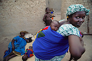 A friend ties her baby to her back with a piece of fabric after an afternoon visit with Pama Kondo in the Natomo family compound courtyard in the village of Kouakourou, Mali, an isolated community between Djenne and Mopti on the banks of the Niger River. Relaxing with one of her children is Pama, and 11 year old Pai leans against the mud brick wall. Published in Material World, page 18. The Natomo family lives in two mud brick houses in the village of Kouakourou, Mali, on the banks of the Niger River.