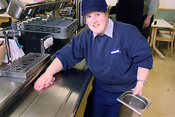 Woman with learning disability wiping surfaces down in canteen,
