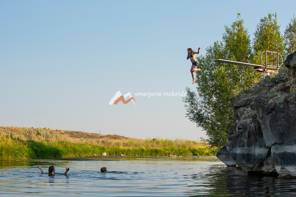 Girl jumping from diving board at the Ledges swimming hole in Richfield, Idaho.