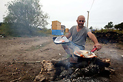 Man cooking fish 'the Jungle' migrant camp in Calais, France, August 10, 2015. The Calais jungle is the nickname given to a series of camps in the vicinity of Calais, France, where migrants live while they attempt to enter the United Kingdom illegally by stowing away on lorries, ferries, cars, or trains travelling through the Port of Calais or the Eurotunnel Calais Terminal. The migrants are a mix of refugees, asylum seekers and economic migrants from Darfur, Afghanistan, Syria, Iraq, Eritrea and other troubled areas of the world.
