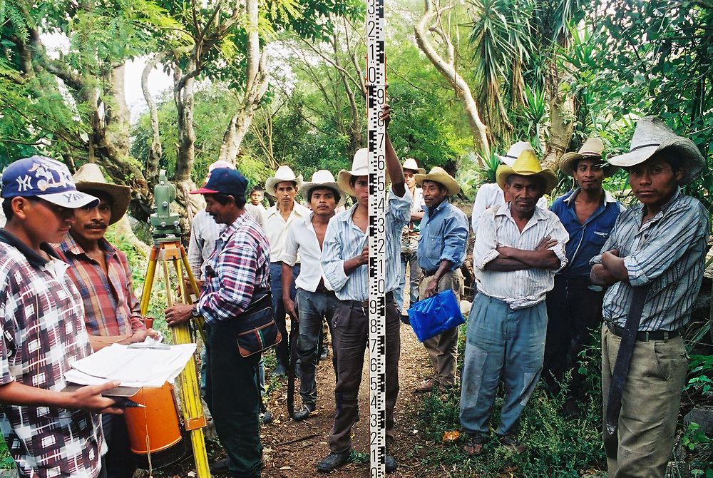 Maya Chortí men help a water engineer take topographic readings for a drinking water system. The water system was never built because of threats from local landowners.