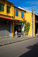 A old woman walks outside her house in the morning, her shadow flows on sidewalk under yellow sunshine. Hoi An, Vietnam, Asia, 2012.