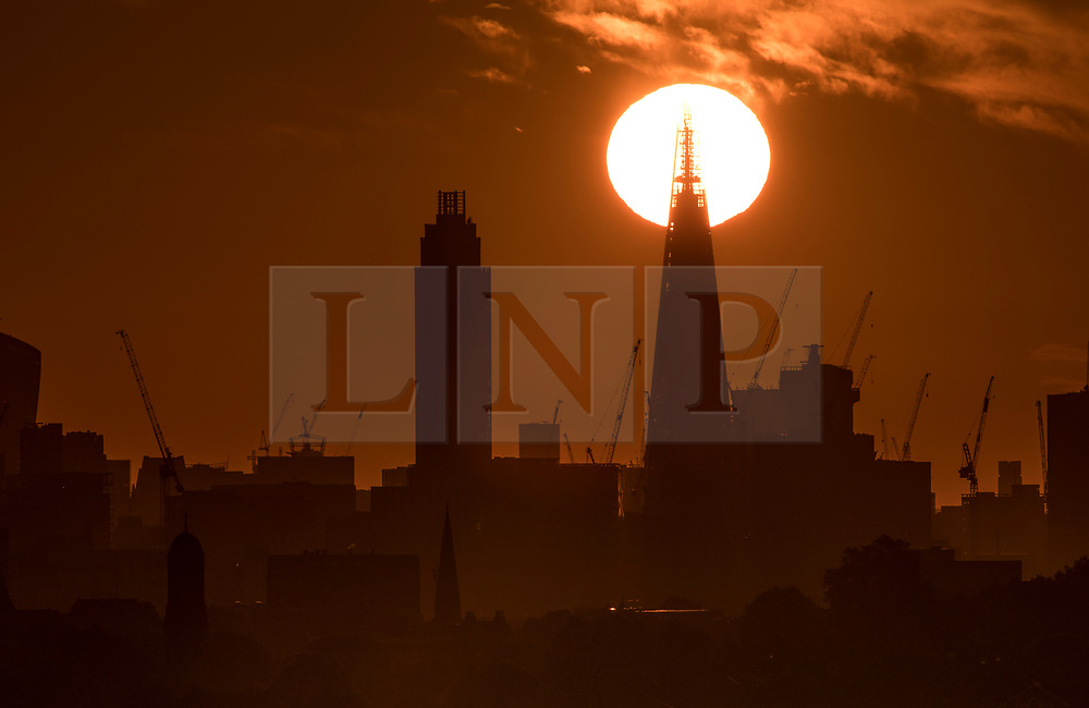 © Licensed to London News Pictures. 21/06/2018. London, UK. The summer solstice sun rises behind The Shard at the start of the longest day of the year. A period of hot and sunny weather is forecast for much of the UK over the next 10 days. Photo credit: Peter Macdiarmid/LNP