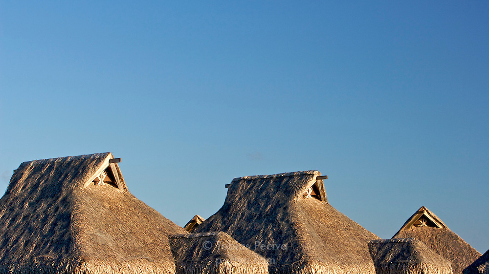 Thatched roof bungalows at the Bora Bora Nui Resort & Spa. Previously a Starwood Luxury Collection property, the Bora Bora Nui is now operated by Hilton. Bora Bora is one of the Leeward Islands in the Society Islands archipelago of French Polynesia.