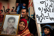 A woman holds up a photo of her son she says was killed by Qadaffi in Banghazi on Feb. 25, 2011.