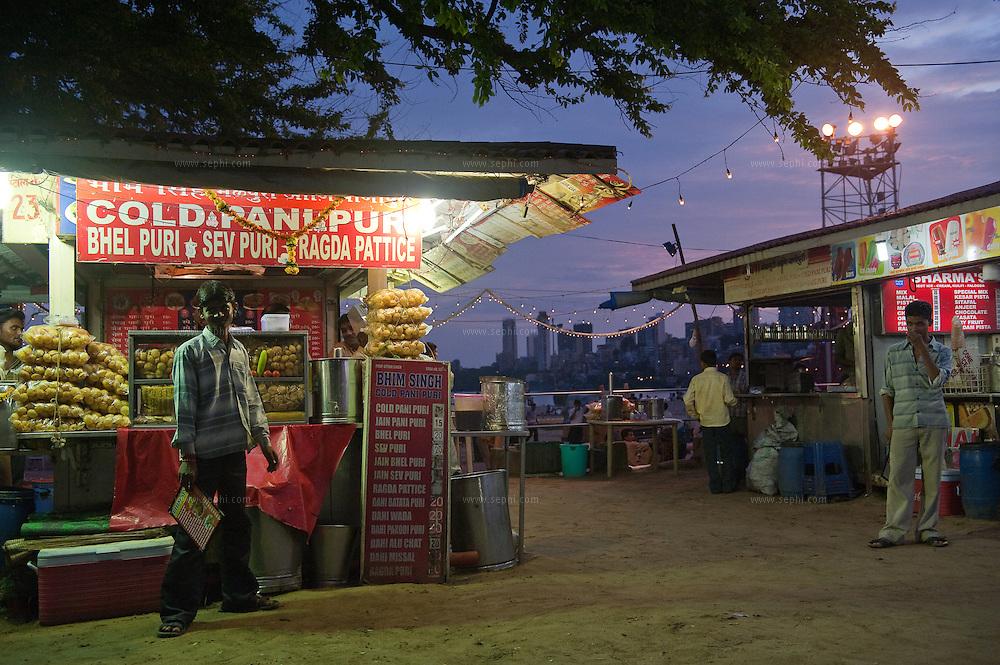 Street food stalls on Chowpati beach in Mumbai offer a variety of favorite snacks like Pani puri, Bhel puri, Sev Puri and more.