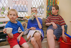 Three boys with autism sitting in front room,