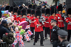 ©  London News Pictures. 21/04/2016. Windsor, UK. Members of the Coldstream Guards march ahead of a walkabout by Queen Elizabeth II through the town of Windsor, Berkshire on the day of her 90th birthday.  Photo credit: Ben Cawthra/LNP