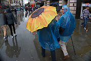 London, UK. Sunday 23rd August 2015. Heavy summer rain showers in the West End. People brave the wet weather armed with umbrellas and waterproof clothing. Sunflower umbrella.