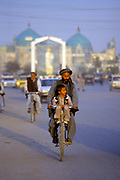 A father and son ride a bike, Mazra-i-Sharif, Afghanistan
