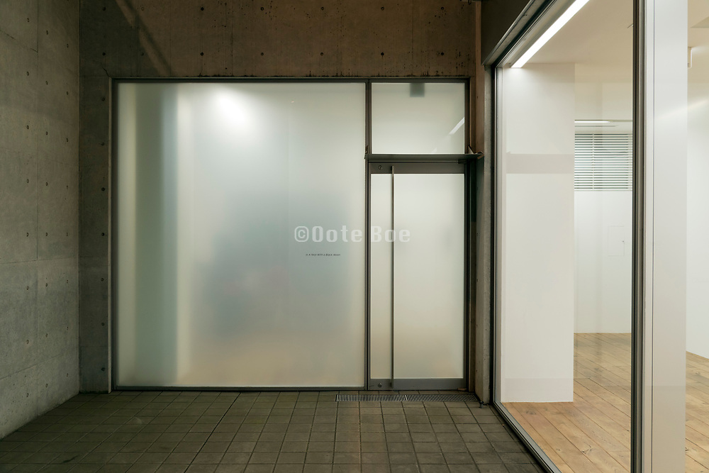 large glass wall with door lighted during night time at the RAT HOLE Gallery in Tokyo