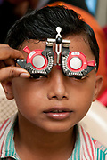 India. Orissa. Trilochan Netralya eye charity. Young boy having his eyes tested.