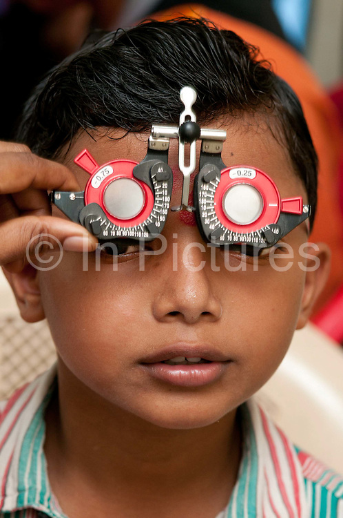 India. Orissa. Trilochan Netralya eye charity. Young boy having his eyes tested.