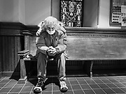 """15 MARCH 2020 - DES MOINES, IOWA: A man wearing a surgical mask prays by himself in the vestibule of a Catholic church in Des Moines. The Des Moines diocese announced that Catholics in Des Moines were """"relieved of the Sunday Mass obligation"""" because of fears over the Coronavirus. Most churches in the Des Moines area canceled their Sunday services or switched to an online service this week. Those churches that conducted Sunday services imposed """"social distancing"""" guidelines, including no physical contact, and had significantly lower attendance. The Governor of Iowa announced Saturday night that the Coronavirus in Iowa had entered the """"community spread"""" phase when a person in Dallas County, in the Des Moines metropolitan area, tested positive for Coronavirus. This is the first reported case in the Des Moines area. As of Sunday morning, Iowa was reporting 18 people tested positive for Coronavirus.            PHOTO BY JACK KURTZ"""